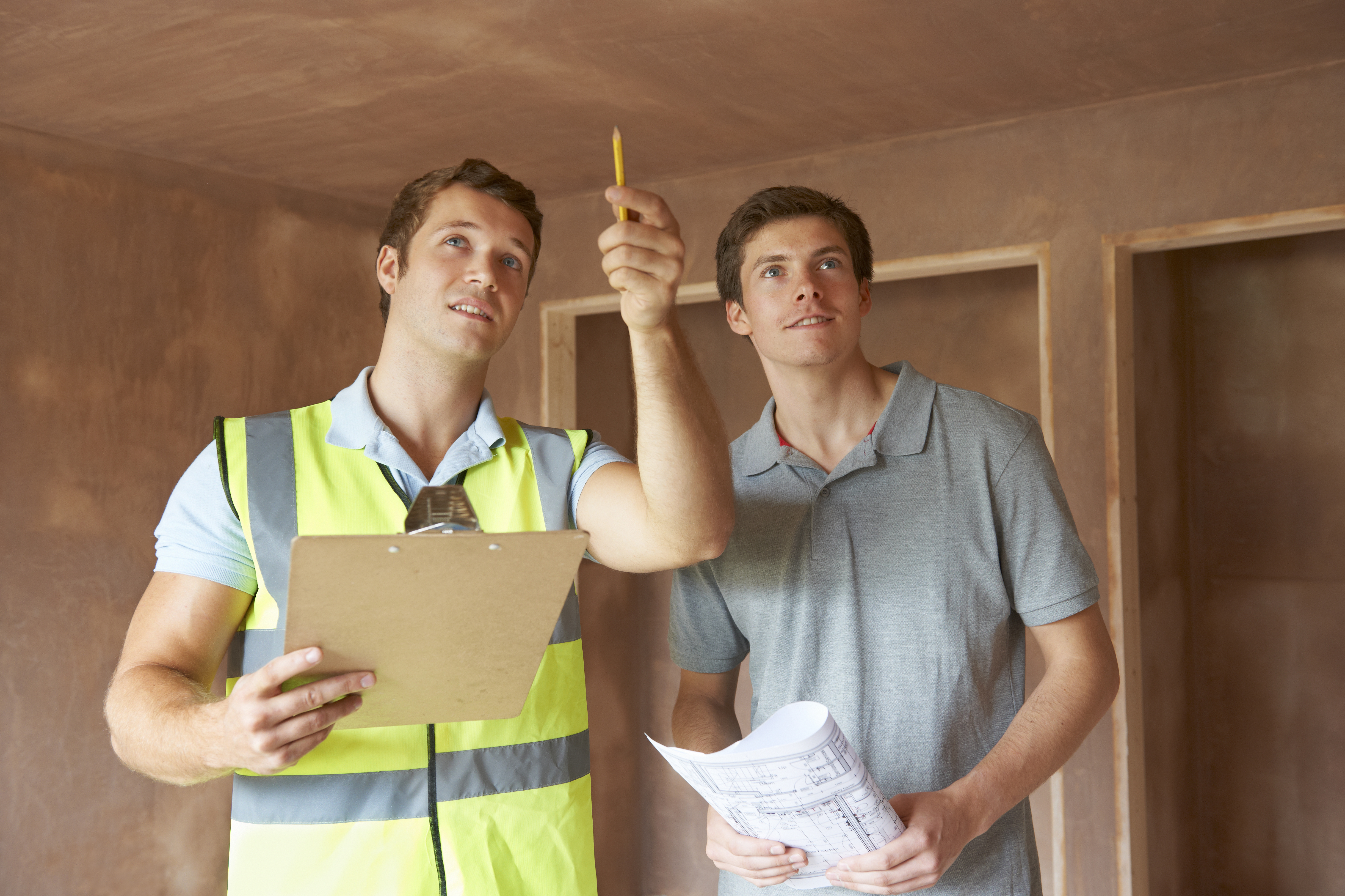 Builder And Inspector Looking At New Property XL Regular Inspections