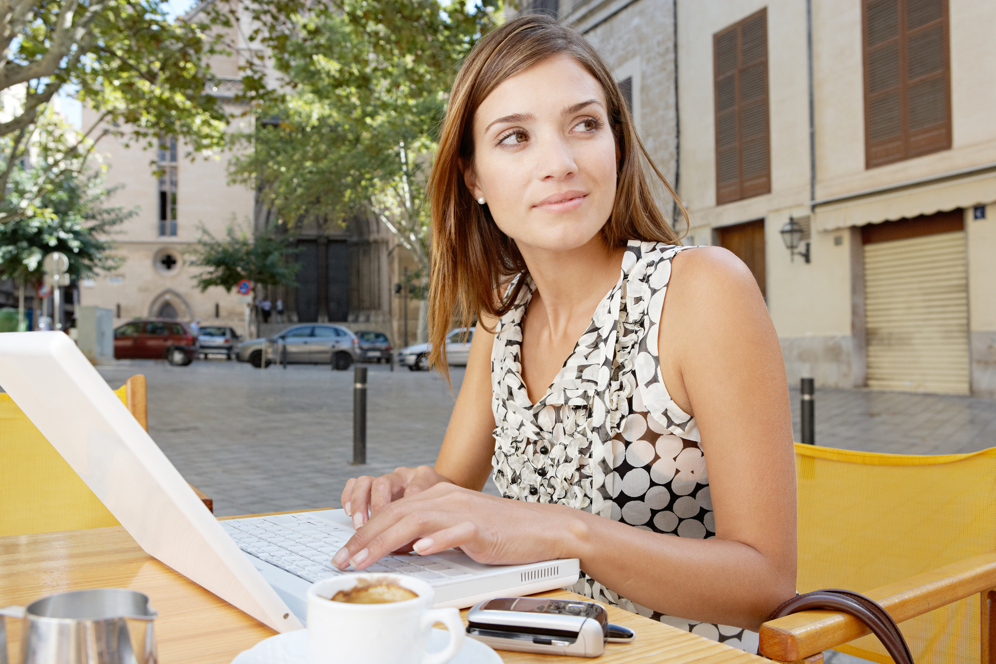 Businesswoman using a laptop computer while having a coffee in a coffee shop terrace