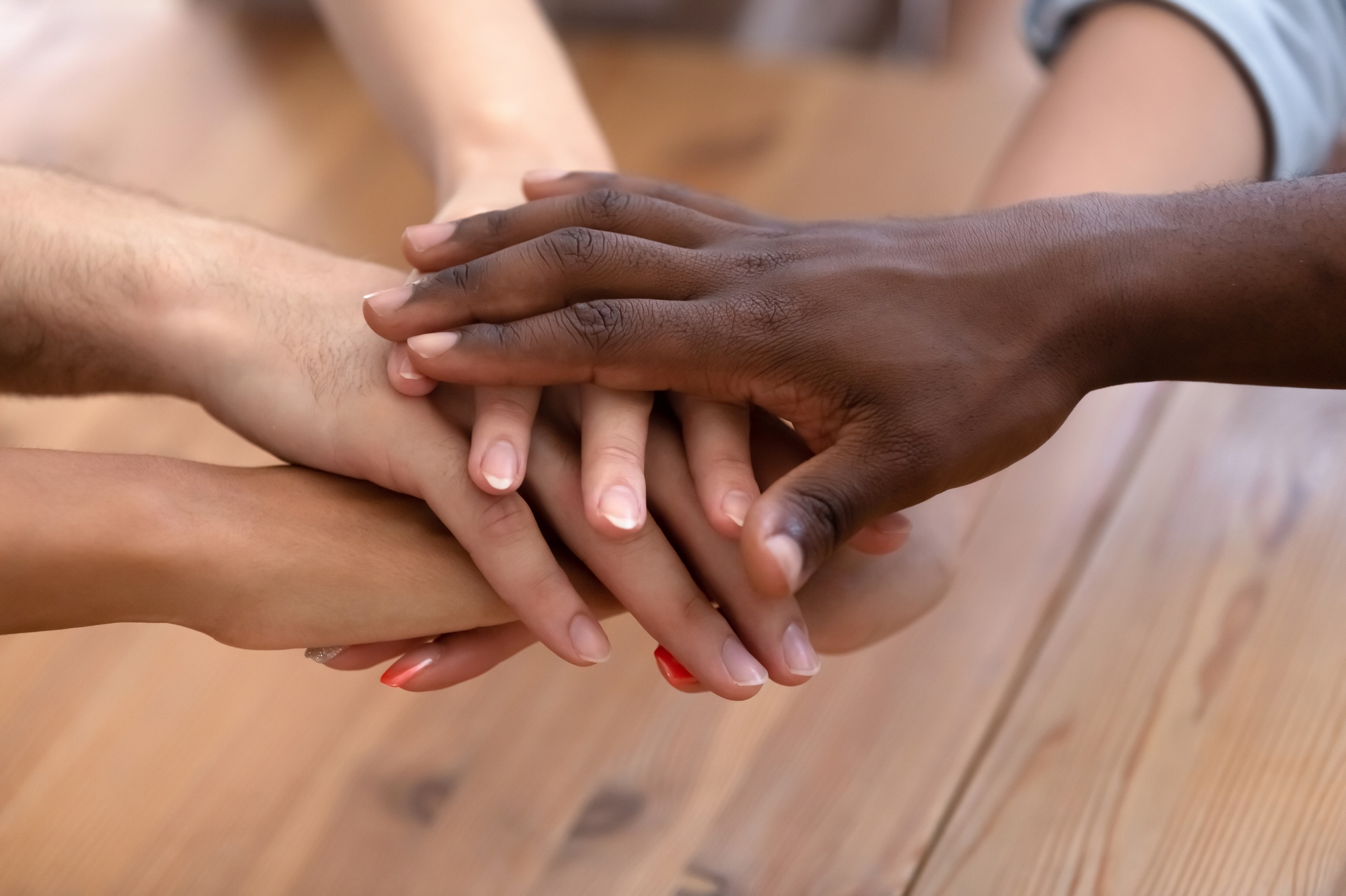 Close up heap of diverse people stacked palms together