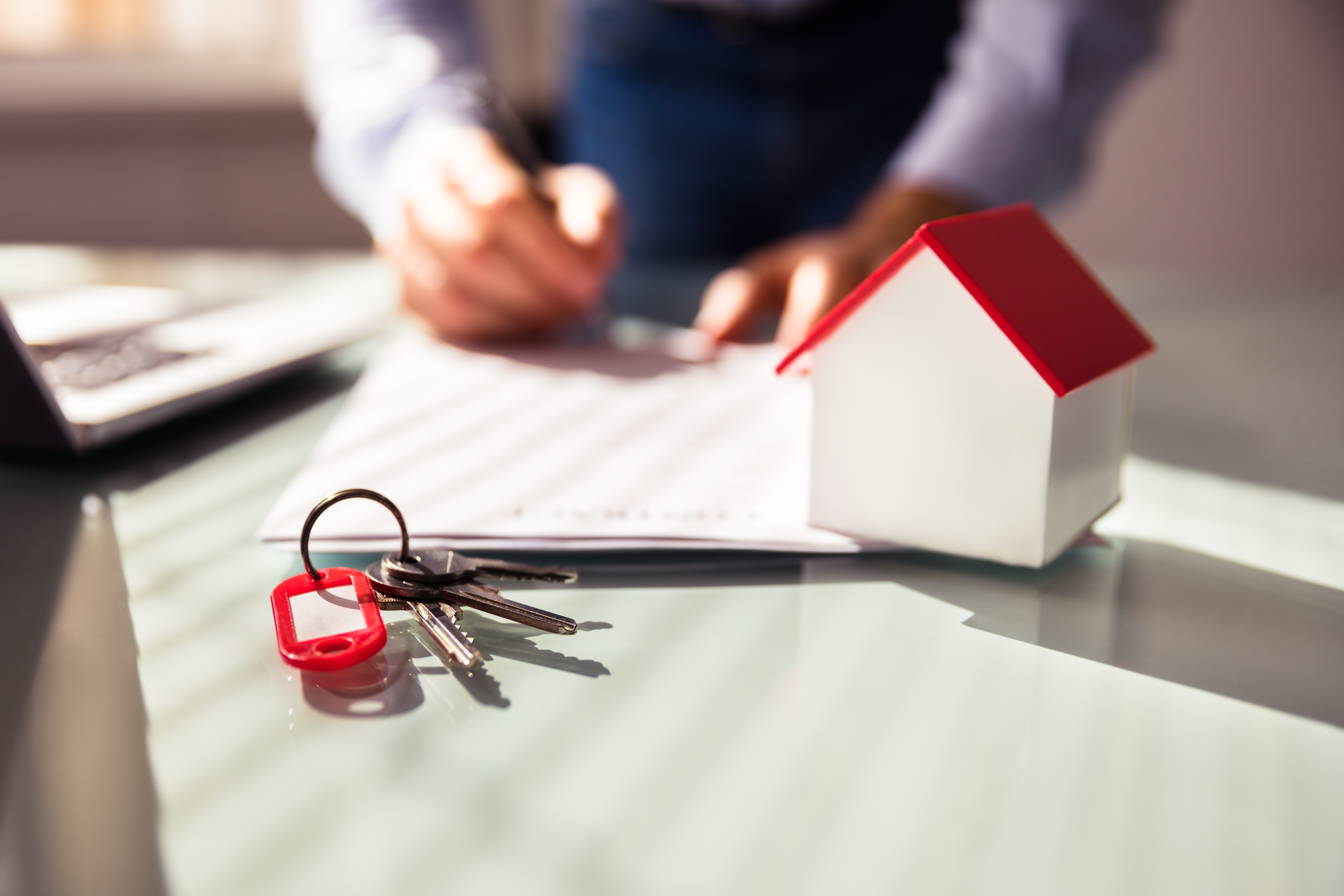 Close up Of House Model And Key Near Human Hand Signing Contract Property Manager