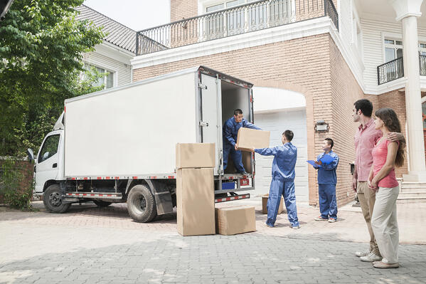 Couple watching movers move boxes from the moving van-1