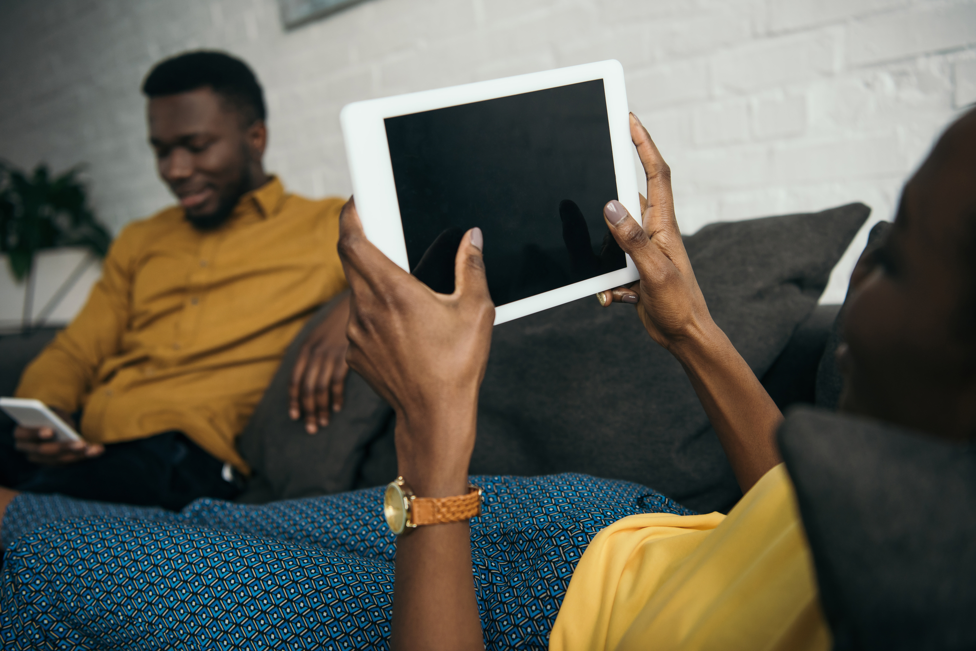 Cropped shot of young woman lying on sofa with digital tablet while boyfriend using smartphone
