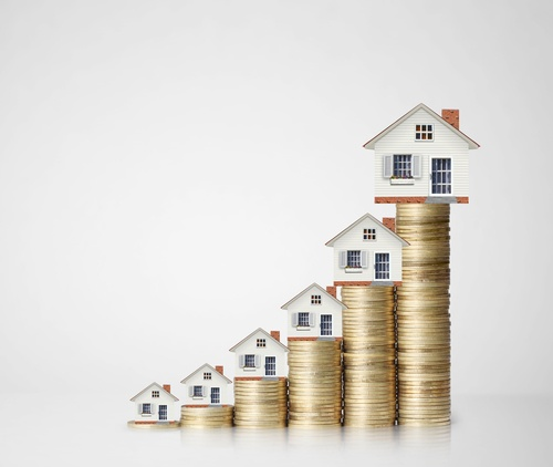 stacks of coins with houses getting bigger left to right property manager