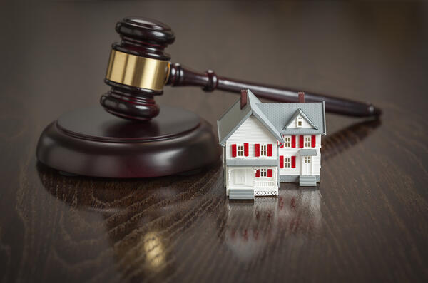 Judge's gavel on a desk next to a small house model Tenant Screening