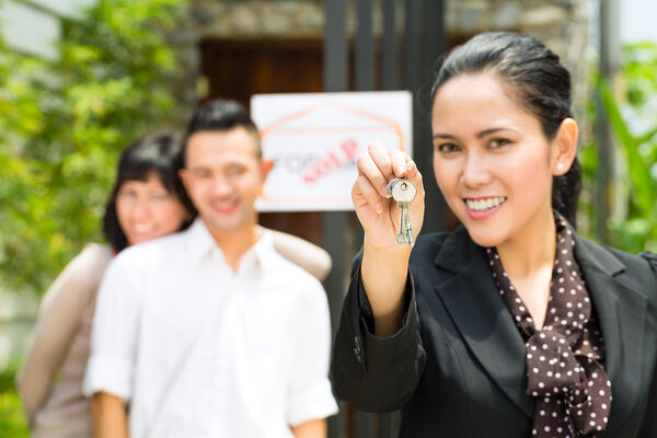 A woman holding keys with a man and a woman in the background, fair housing act