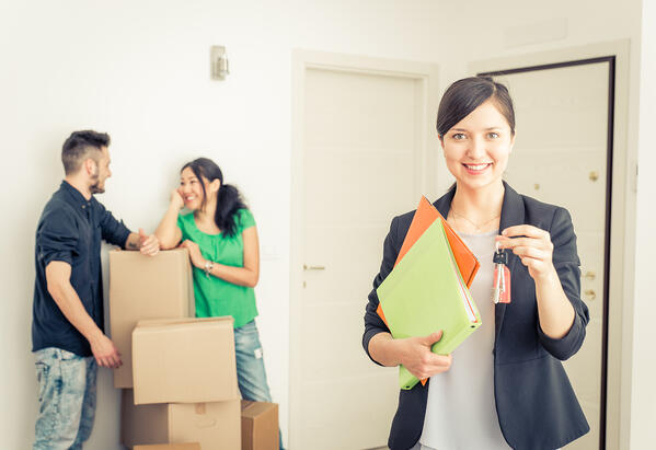 Woman holding keys and binders while couple stands with boxes behind her Property Manager