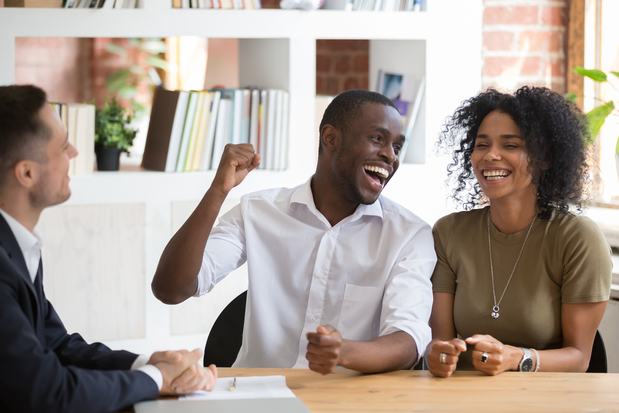 Excited black couple feel euphoric closing deal with realtor