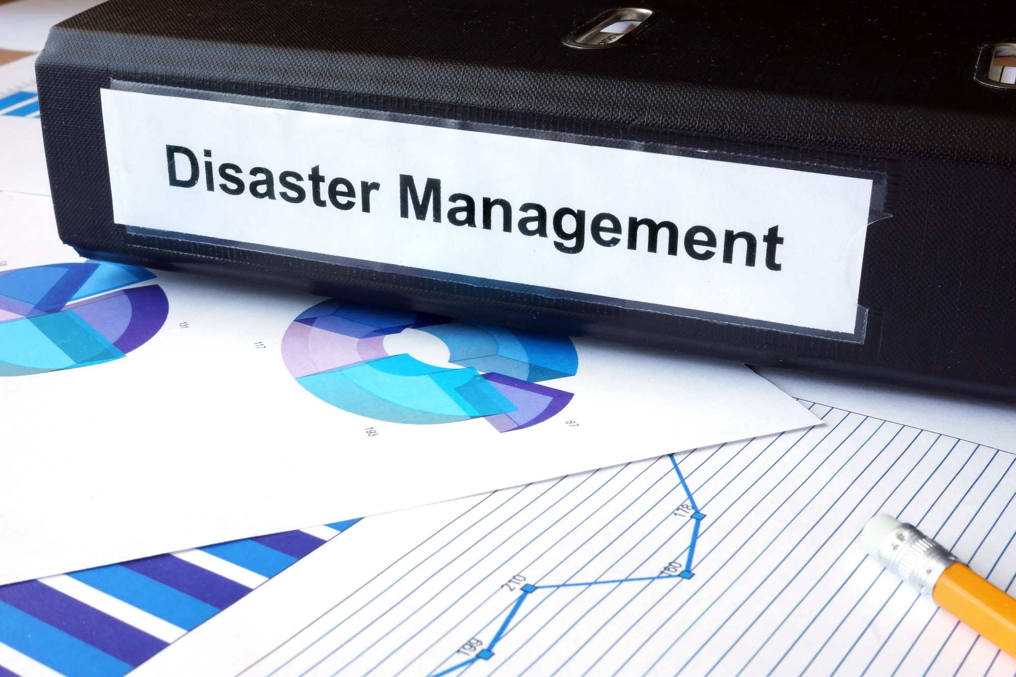 Graphs and file folder with label Disaster Management