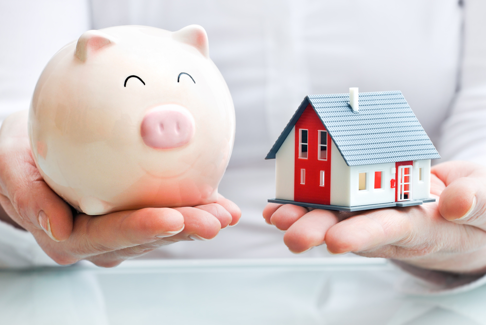 Hands weighing a piggy bank and a house, value concept Real Property Management