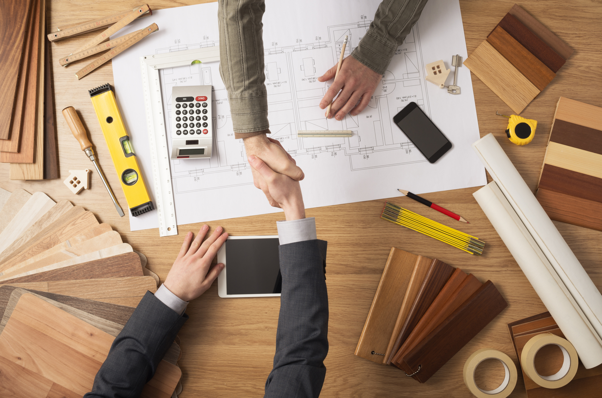 Handshake over tools and building plans Property Management