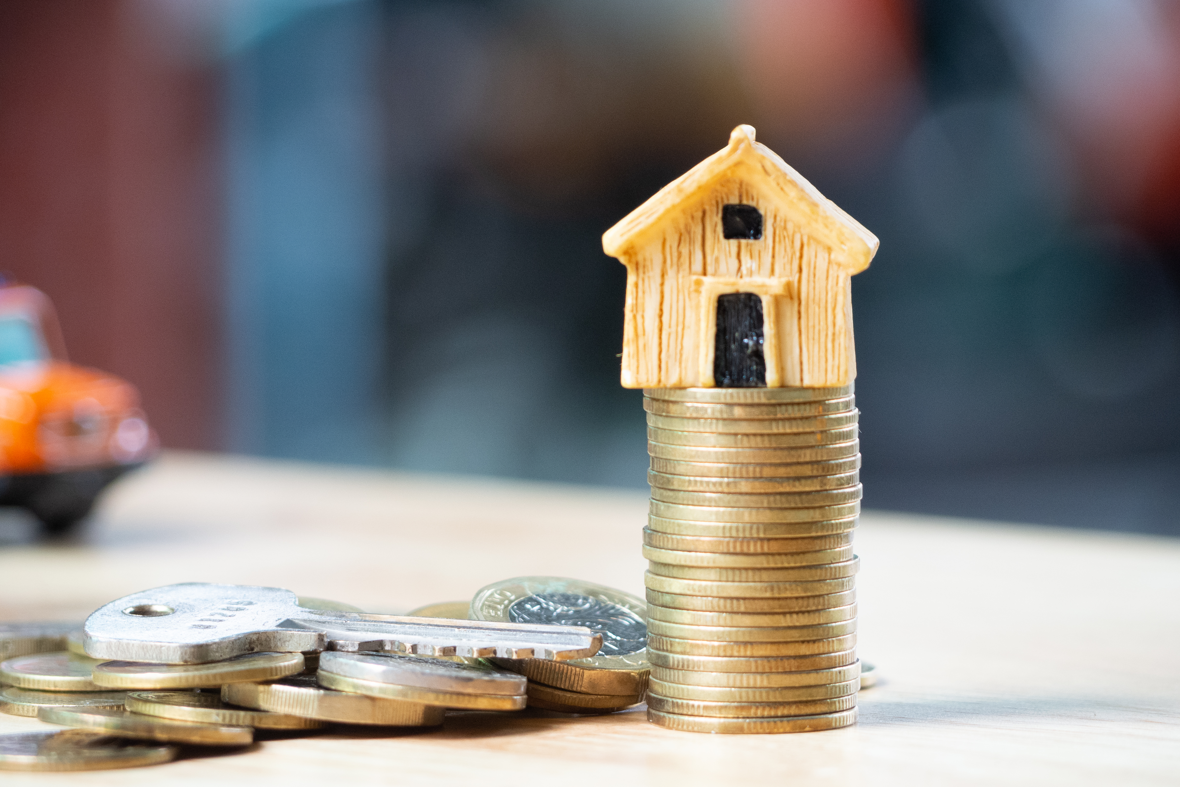 House or Home model on near of coins stack with home key. Concept for loan, property ladder, financial, mortgage, real estate investment, taxes and bonus, investment property