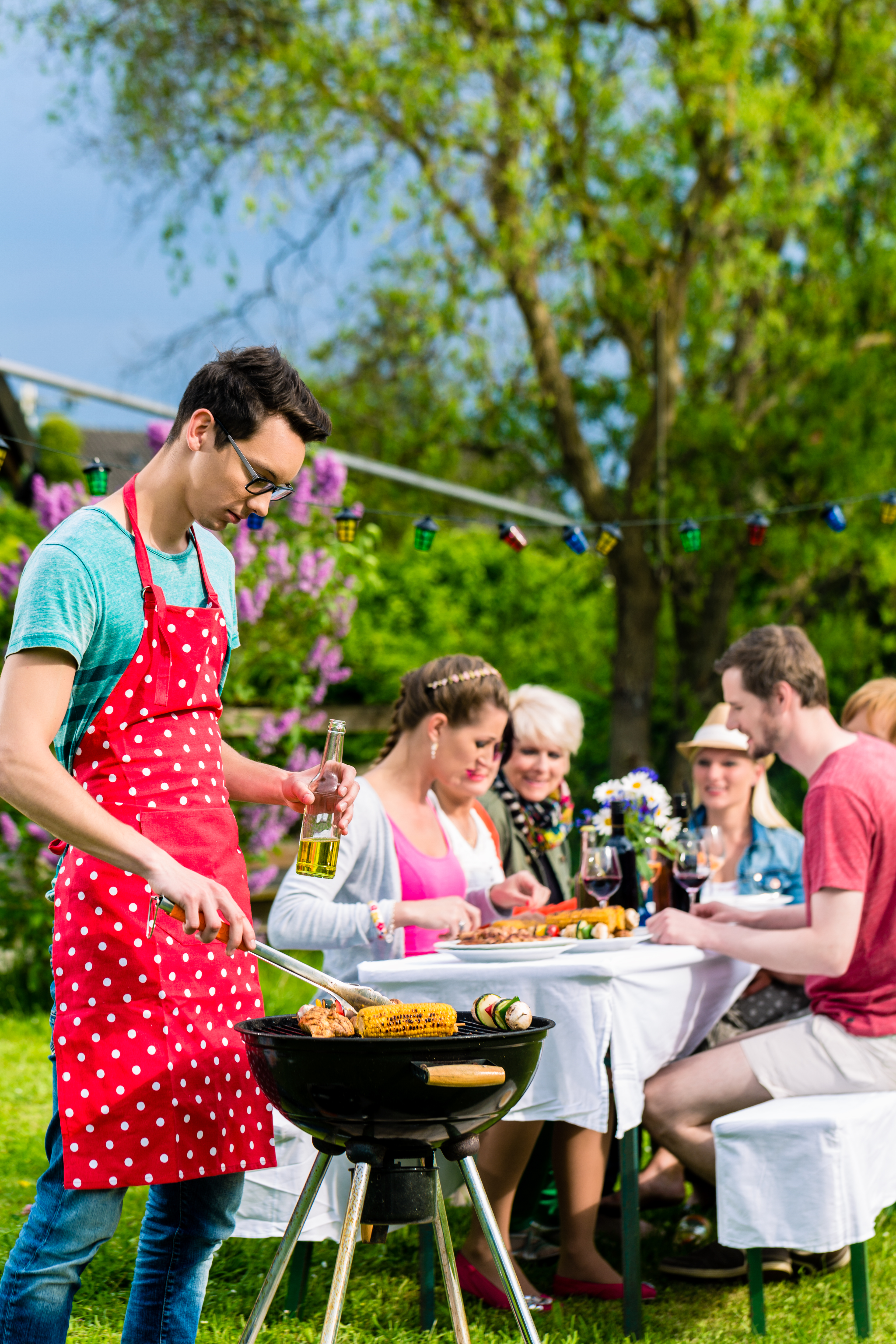 Man grilling meat on garden barbecue party, property management