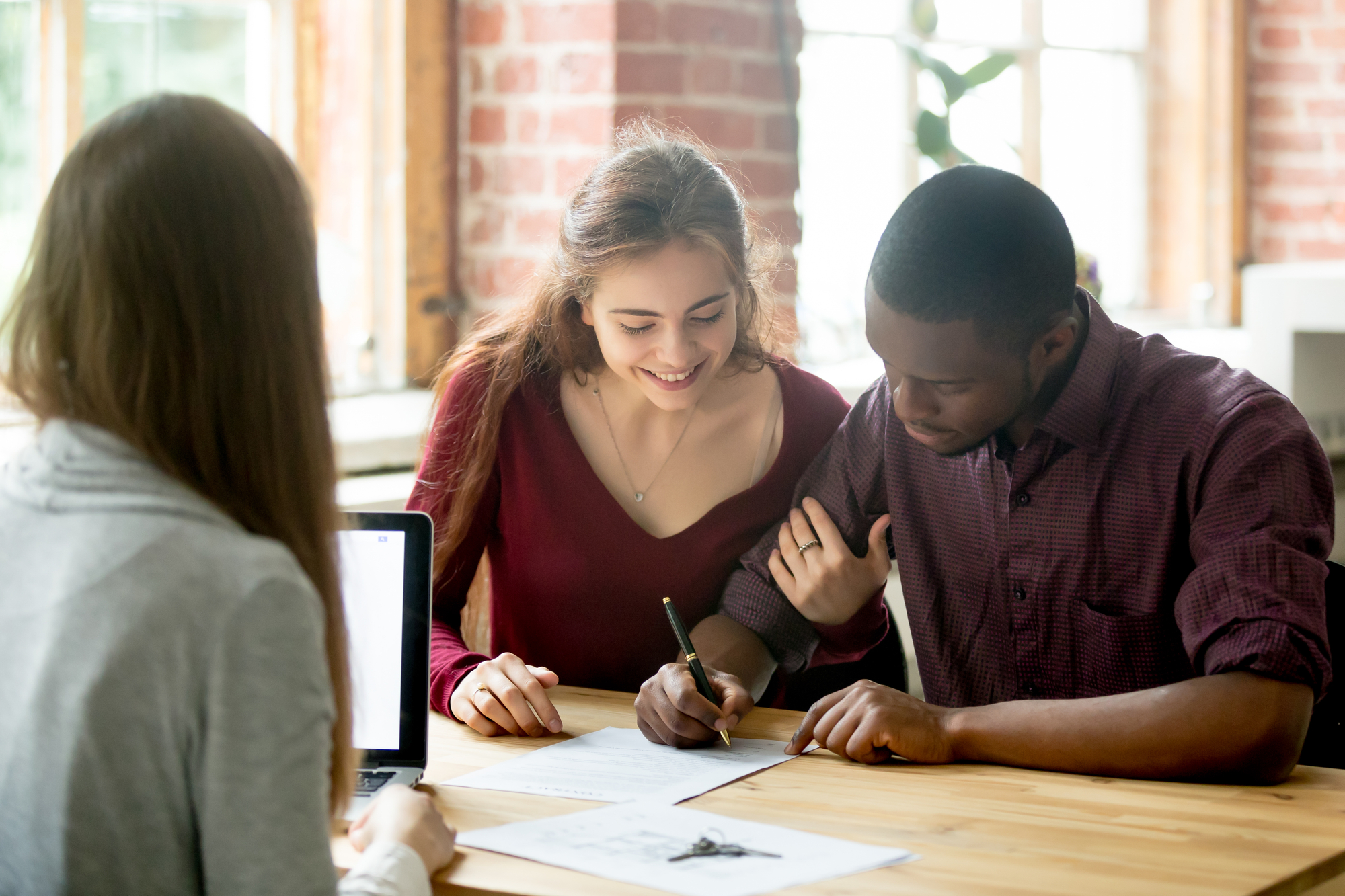 Multiracial couple signing deal from real estate agent