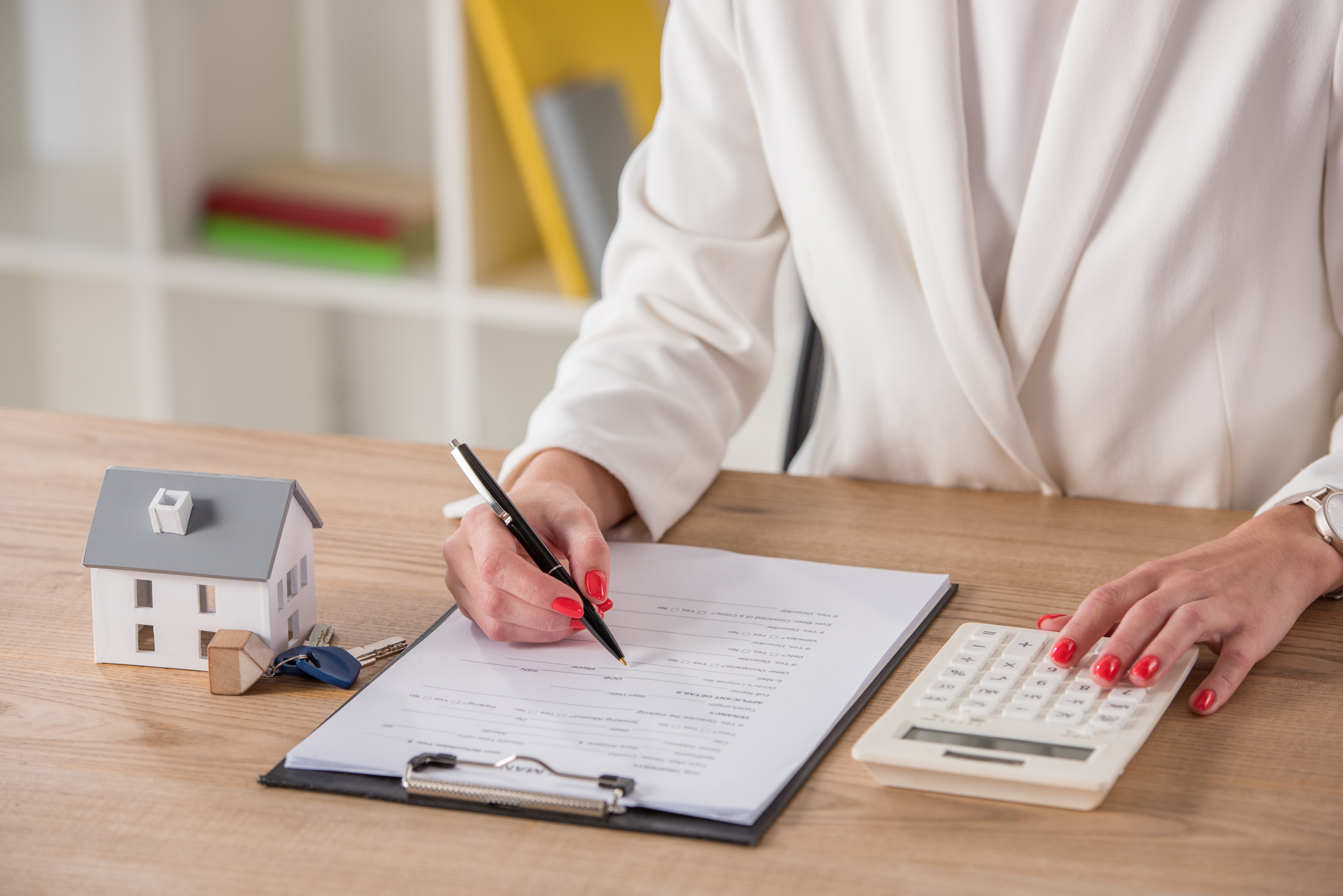 Partial view of businesswoman using calculator and writing in contract near house model and keys