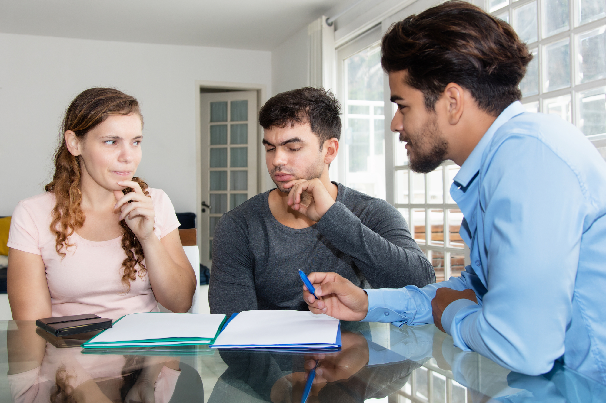 Skeptical couple with contract and agent Residential Property Management