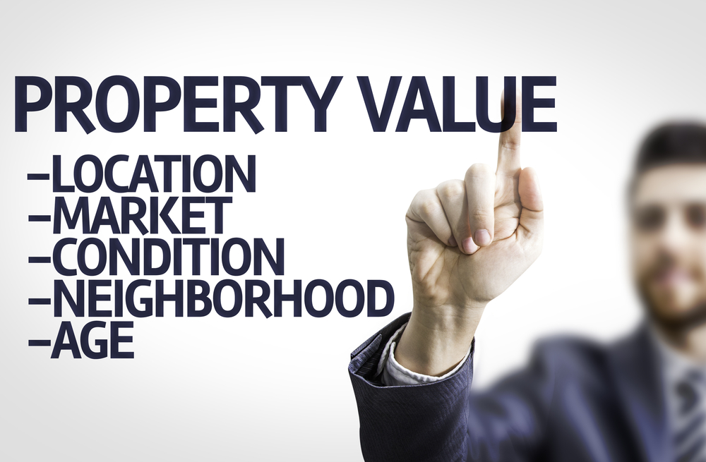 Business man pointing to transparent board with text Property Value, property management