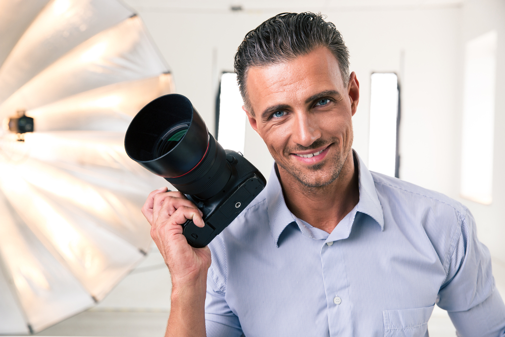 Portrait of a handsome photographer holding camera and looking at camera in studio Property Management Company