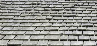 Thick wooden shingles on roof of historical restoration of pioneer prairie cabin of the 1830s in northern Illinois Spring Maintenance
