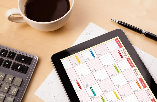Workplace with tablet pc showing calendar and a cup of coffee on a wooden work table close-up, manage rental properties