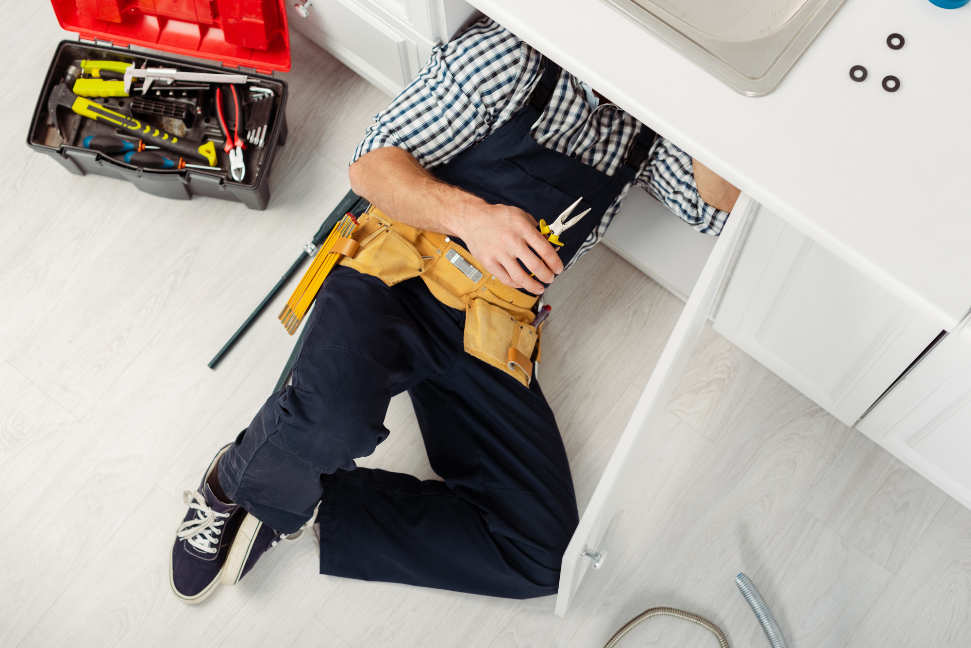 Top view of handyman in overalls and tool belt holding pliers while repairing sink in kitchen
