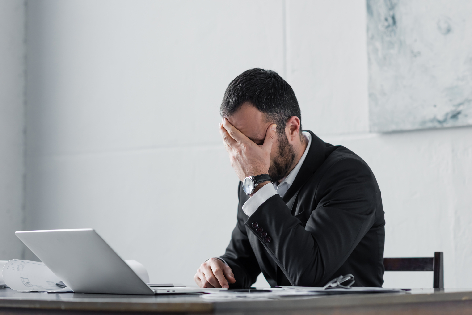 Upset businessman holding hand on face while sitting at workplace