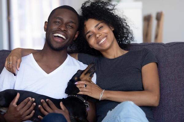 cute couple with a puppy in their lap tenancy screening